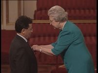 Queen Elizabeth appends the OBE medal to Professor Toro