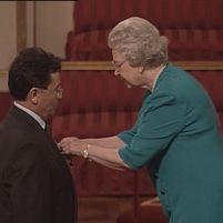 Queen Elizabeth appends the OBE medal to Professor Toro